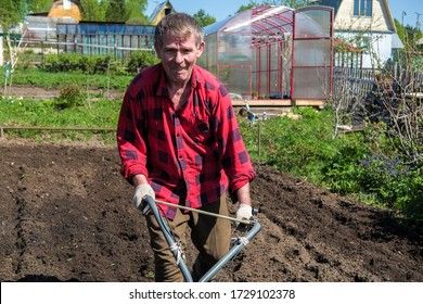 Old man plows the ground with a motor cultivator. A farmer ploughs the soil using a petrol cultivator.