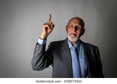 Old man is pointing at something interesting on grey background.