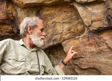 Old man points at the ancient bushman paintings. Shot in Hottentots Holland Mountains, Vergelegen area, near Somerset West, Western Cape, South Africa.