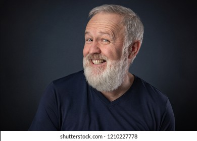 Old man portrait with gray beard on blue background playing and pretending to laugh