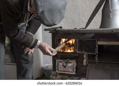 Old man is putting wood a heating stove in a country house in Eskisehir, Turkey