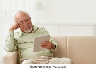 Old man reading book on tablet computer at home