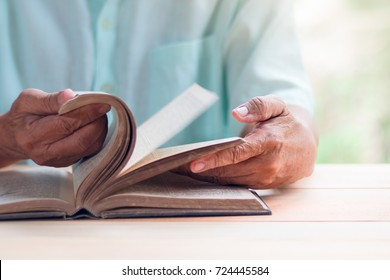 old man reading book on light brown wooden table surface, flipping movement, selective focus