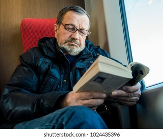 An old man is reading a book in a train near the window