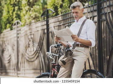 Old man Reading Newspaper near Bicycle in Park. Relaxing in Park. Active Rest Concept. Riding on Bicycle. Smiling Grandfather. Man with Gray Hair. Healthy Lyfestyle in Summer. Summer Park