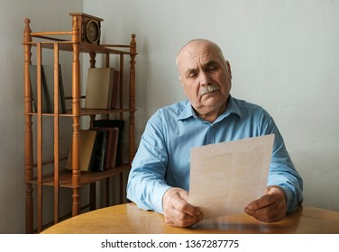 Old man reading a paper document or letter with a look thoughtful look of concentration as he sits at a table indoors