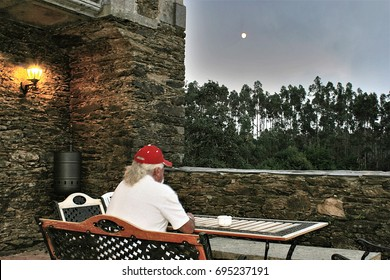 Old man with red cap sitting looking at the full moon,  peace, calm, serenity, harmony, fullness, well-being, nature, natural, contemplate, meditate, breathe, grow, happiness, tranquility, plenitude,
