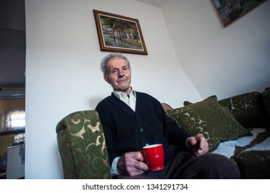 Old man with a red mug