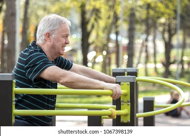Old man resting after doing physical exercises in the fitness park