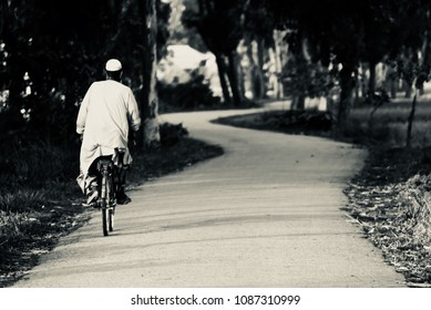 An old man is riding a bicycle on an empty urban road isolated unique photograph