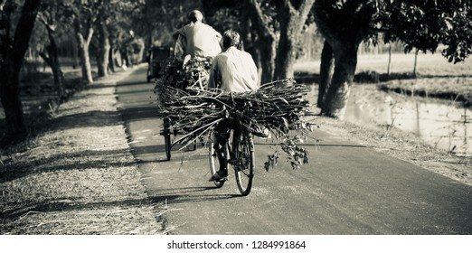 An old man riding a bicycle on the urban road