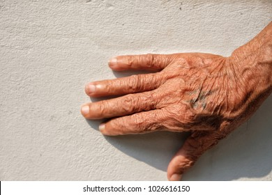 old man right wrinkle hand with old tattoo on white wall background