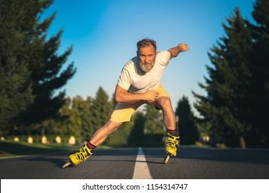 The old man rollerblading on the asphalt