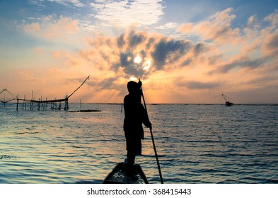old man rowing a boat on a lake at sunrise