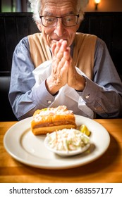 Old man rubs his hands in anticipation of eating the food in front of him. Restaurant setting. Happy man wearing a nice shirt and sweater. He's hungry and excited about the lobster roll on his plate.