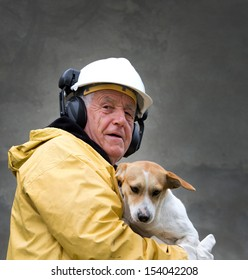 Old man in safety suit holds dog in his arms