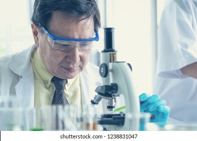 old man Scientist using microscope in laboratory
