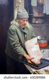 An old man seasoning a large piece of pork and preparing it for the oven.