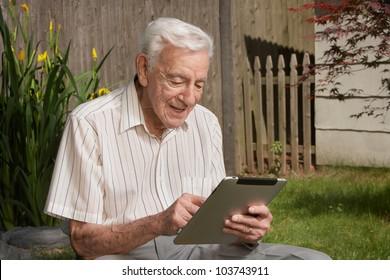 Old man senior citizen using tablet computer