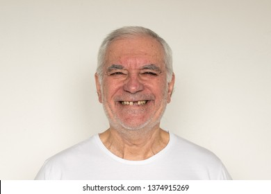 old man senior face closeup missing tooth smile proper tooth overexposed not in focus