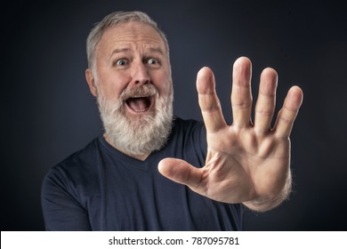 Old man in shirt and scared with his stretched hand forward