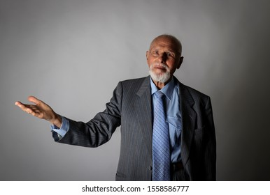 Old man is showing at something interesting on grey background.