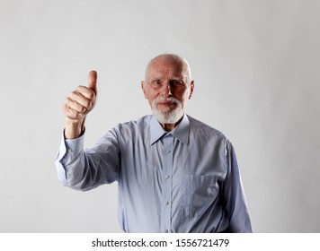 Old man is showing thumb up. Success, happiness and good health.