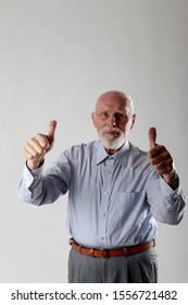 Old man is showing thumbs up. Success, happiness and good health.