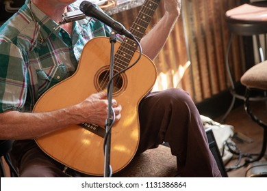 Old man singing and playing folk country music with guitar and harmonica.