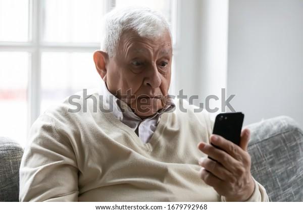 El anciano sentado en el sofá sostiene el smartphone mirando la pantalla del dispositivo se siente confundido por el mensaje de SMS recibido. La generación más antigua y los modernos gadgets dificultan el uso de aplicaciones, células rotas, necesitan un concepto de reparación