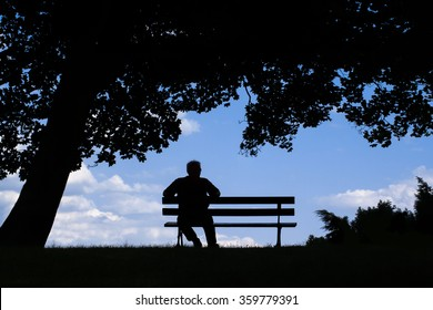 old man sitting alone on park bench under tree