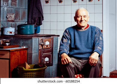 Old man sitting by his tile stove