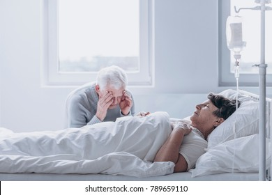 Old man sitting by his elderly wife, losing faith in her getting better