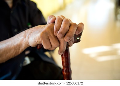 Old man sitting with his hands on a wooden walking stick.