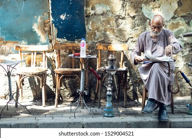 An old man sitting in a local coffee shop having tea and shisha (hoka) in Cairo, Egypt. in September 2019