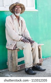 A old man is sitting on a bench outside of his home.