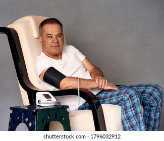 Old man sitting on the couch measures blood pressure at home. Means of coronavirus prevention and treatment. Covid-19. Concept of health.