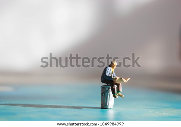 Old man sitting on garbage or trash can reading a newspaper. Fake news depicted in miniature with dramatic shadows.