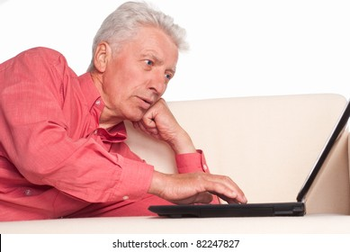 old man sitting on sofa with laptop