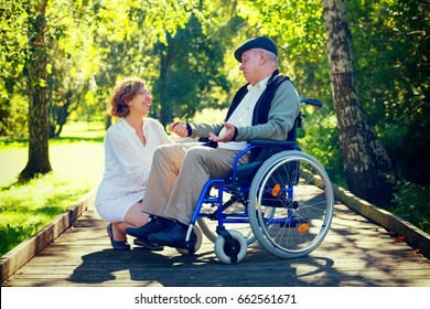old man sitting on wheelchair and talking to young female medical assistant in the park