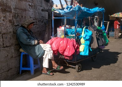 Old man sleeping on the chair near his cart with colorfull baggies