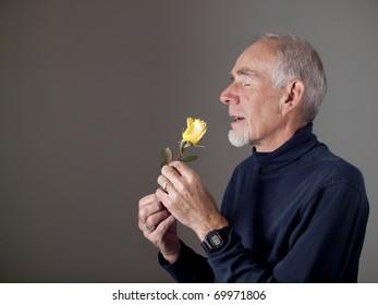 Old man smelling a rose