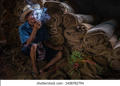 Old man smoking cigarette and the smoke released from the mouth, Bad habits concept.