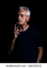Old man is smoking in front of black background