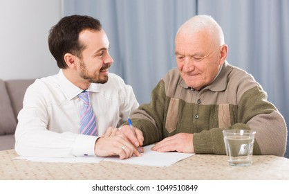 Old man and social department manager fill in questionnaire