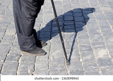 Old man standing on a street with walking cane, shadow on pavement. Concept of disability, old age, overweight, limping person, diseases of the legs