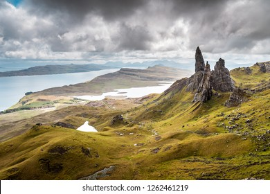 Old Man Of Storr Pinnacles, Scottland, Isle Of Skye - Picturesque mountain backdrop of the Scottish hiking paradise with spectacular rock formation surrounded by lush highland grass