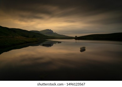 Old Man of Storr reflection in Loch Fada with three boats, Skye, Scotland