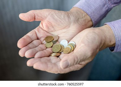 The old man stretches out his hands in which coins lie. Poverty. Russia.