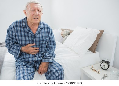Old man suffering with body pain in the bedroom